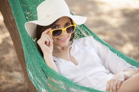 Cute young woman wearing sunglasses resting on a hammock outdoors