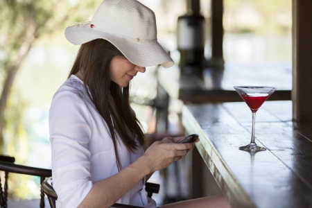 Cute girl updating her social network status while having a cocktail at a bar photo