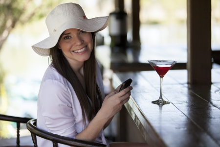 Beautiful young woman sending a text message to her friends while drinking at a bar photo