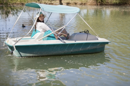 Happy young woman having fun in a pedal boat in a lake photo