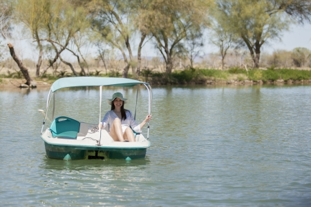 Cute young woman on a pedal boat ride in a lake photo