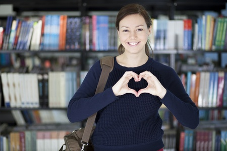Cute young woman at the library making a hearth with her hands and smiling photo