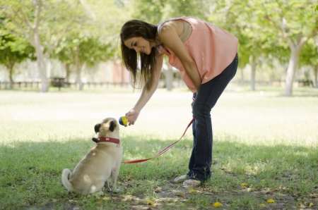 fetch: Cute young woman playing ball with her pug dog at a park