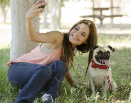 Cute young woman trying to take a picture of her and her dog in a park photo
