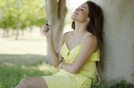 Young beautiful woman listening to music and relaxing at a park photo