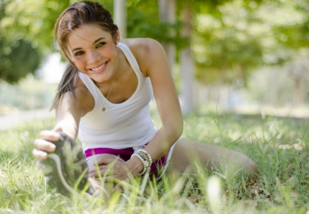 Cute young woman warming up and doing some stretching exercises before running photo