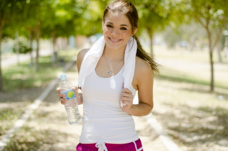 Pretty young woman running at the park and drinking water photo