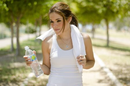Cute young woman cooling down and drinking water while exercising photo