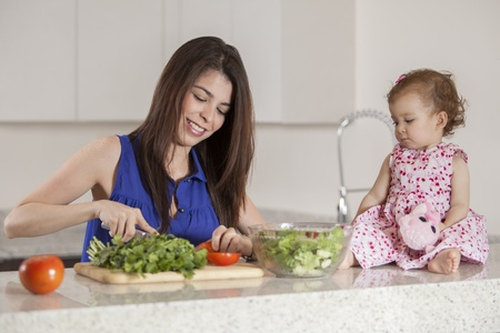 sitter: Young mother and her baby girl making a salad in the kitchen Stock Photo