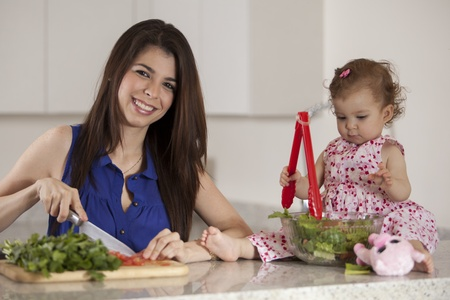 sitter: Cute young mother cooking dinner while her baby girl sits on the counter