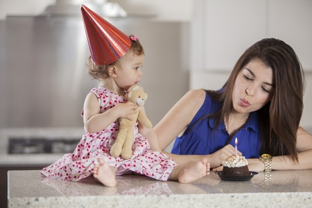 Young mother showing her baby girl how to blow the candle Stock Photo - 18639856