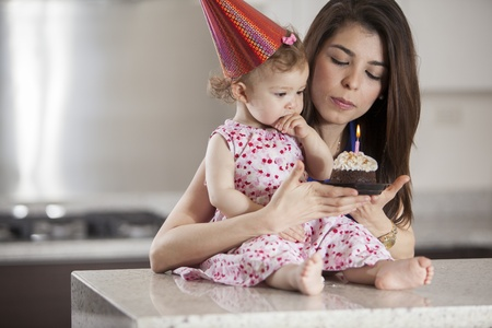 Cute baby girl and her mom blowing the candle of a birthday cake Stock Photo - 18639831