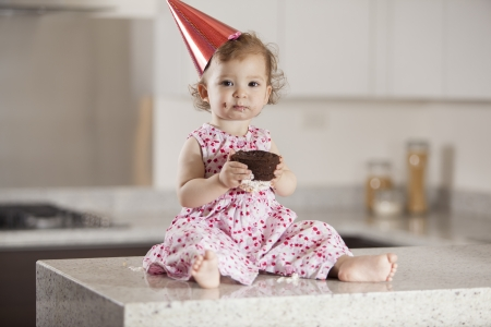 eating: Pretty baby girl celebrating her birthday and eating cake
