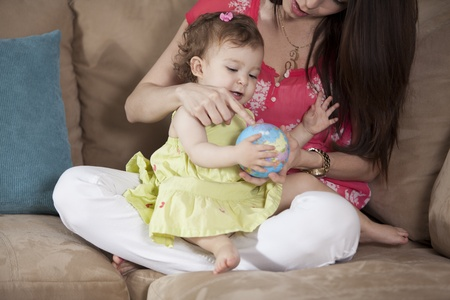 Young mother and baby girl playing with a ball Stock Photo - 18639875
