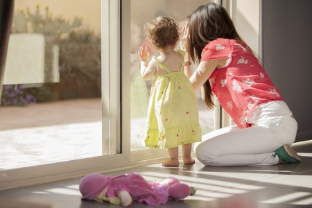 sitter: Cute baby girl and her mother looking outside through a glass door