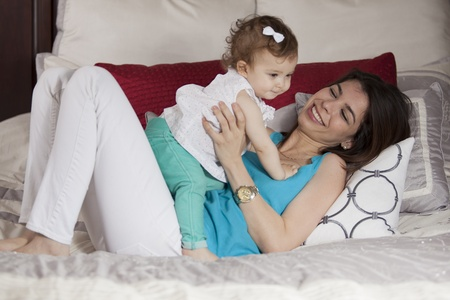 sitter: Cute young mother and baby girl having some fun in the bedroom Stock Photo