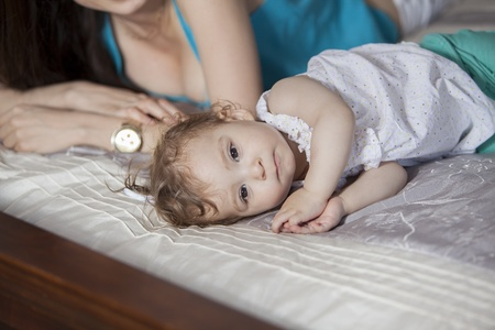 sitter: Cute baby girl taking a nap next to her mom Stock Photo