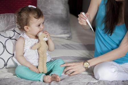bebe enfermo: Comprobaci�n de la temperatura del beb� s Foto de archivo