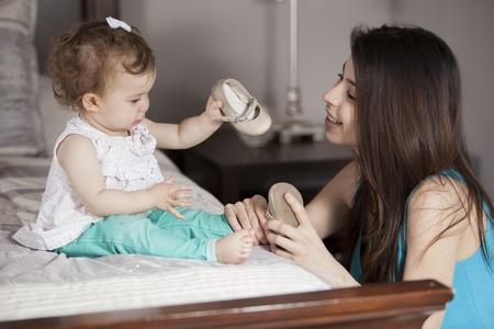 vistiendose: Madre joven que consigue su niña vestida
