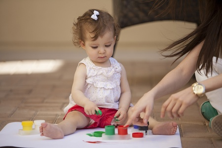 Cute baby girl learning how to paint with her mom Stock Photo - 18639860