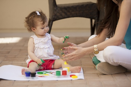 Young mother teaching her baby girl how to paint photo