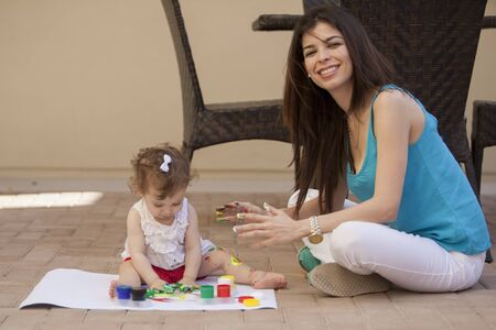 Beautiful young mother and her baby girl learning to paint in the backyard photo
