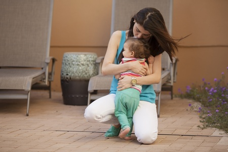 Young mother hugging her cute baby girl outdoors photo