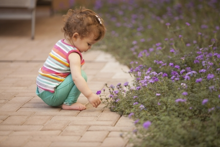 Cute baby girl having fun in the garden