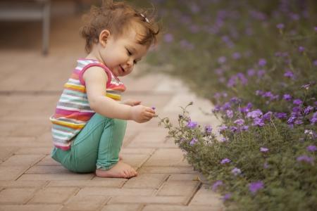 quiet baby: Happy baby girl picking flowers Stock Photo