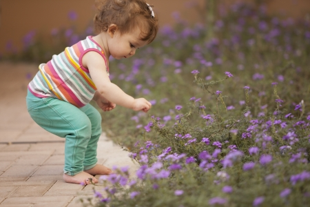 Beautiful baby girl having fun outdoors and picking flowers photo