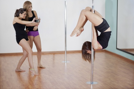 Pole fitness instructor demonstrating a pose while students watch and take photos