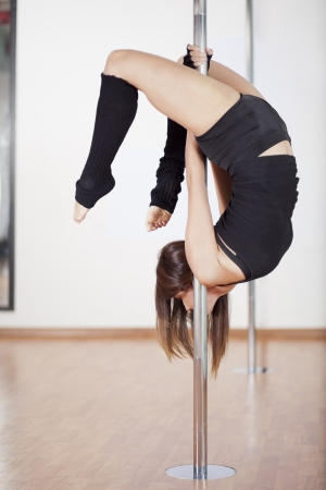 Cute young woman practicing a pose in pole fitness class Zdjęcie Seryjne