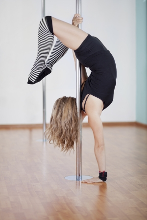 Sexy young woman practicing a new pose at pole fitness class Zdjęcie Seryjne