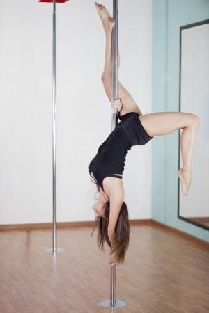 Beautiful young woman working out in pole fitness class Zdjęcie Seryjne