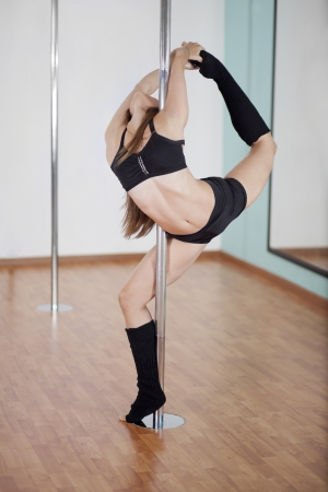 Sexy young woman holding a ballerina pose during pole fitness class