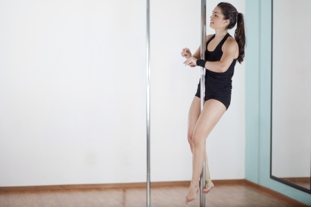 Cute young woman climbing on a pole and getting for her next move on a pole fitness class photo