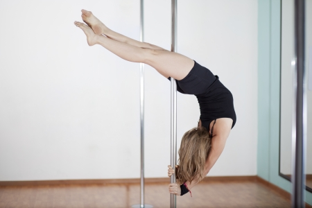moves: Sexy woman working out and practicing some moves in her pole fitness class Stock Photo