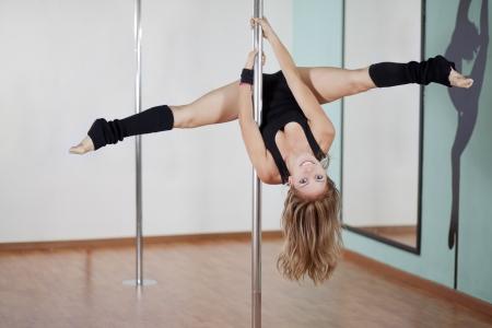 beine spreizen: Nette junge Frau arbeitet und Spaß in ihrem Pole Fitness-Klasse Lizenzfreie Bilder