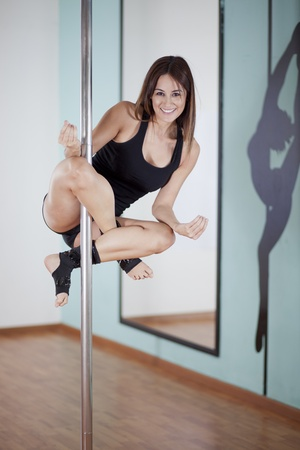 striptease women: Happy young woman working out and having fun in her pole fitness class Stock Photo