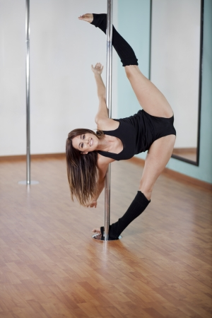 spread legs: Happy young woman working out and posing at pole fitness class Stock Photo