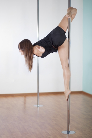 Sexy young woman in pole fitness class