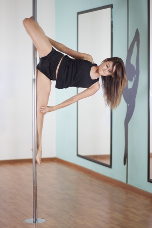 Beautiful young woman practicing a new pose in a pole fitness class Zdjęcie Seryjne