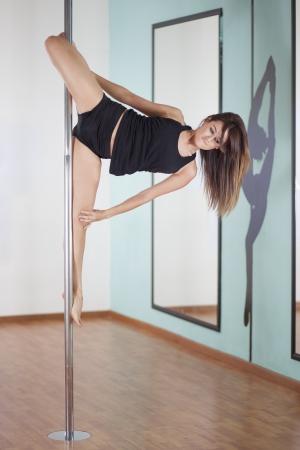 beine spreizen: Schöne junge Frau praktizieren eine neue in der Pole Fitness-Klasse Pose Lizenzfreie Bilder
