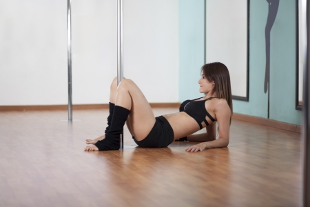Cute young woman resting and taking a break from a pole fitness class photo