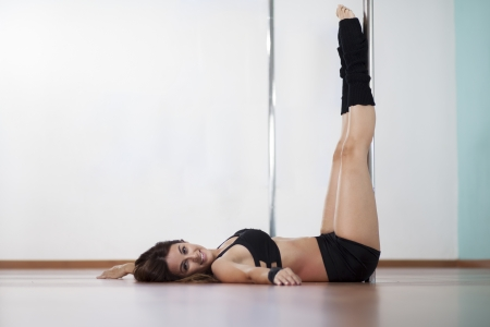 Beautiful young woman warming up for her pole fitness class Zdjęcie Seryjne