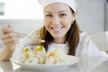 finishing touches: Happy female chef adding the finishing touches to a dish