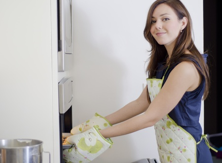 Cute young woman getting cookies out of the oven photo