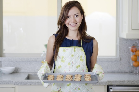 housewife gloves: Cute housewife holding a tray of freshly baked cookies