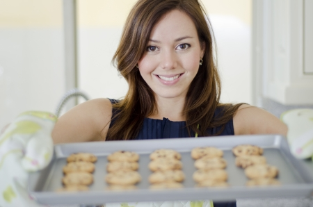 Cute young housewife holding a tray of delicious cookies photo