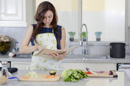 Young housewife cooking a recipe in the kitchen
